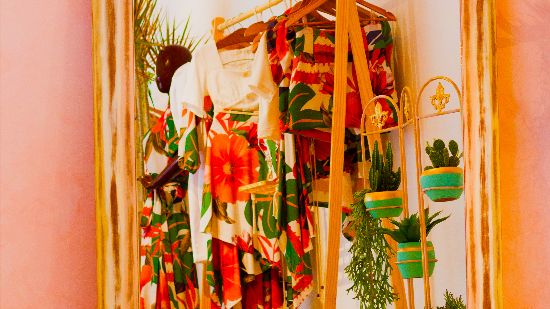 Rack of vibrant clothing with potted plants