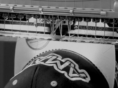 Black and White Image of Melco Embroidery Machine embroidering onto a cap