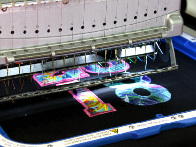 """Melco Embroidery Machine with 11x13"""" Mighty Hoop embroidering the number 18"""