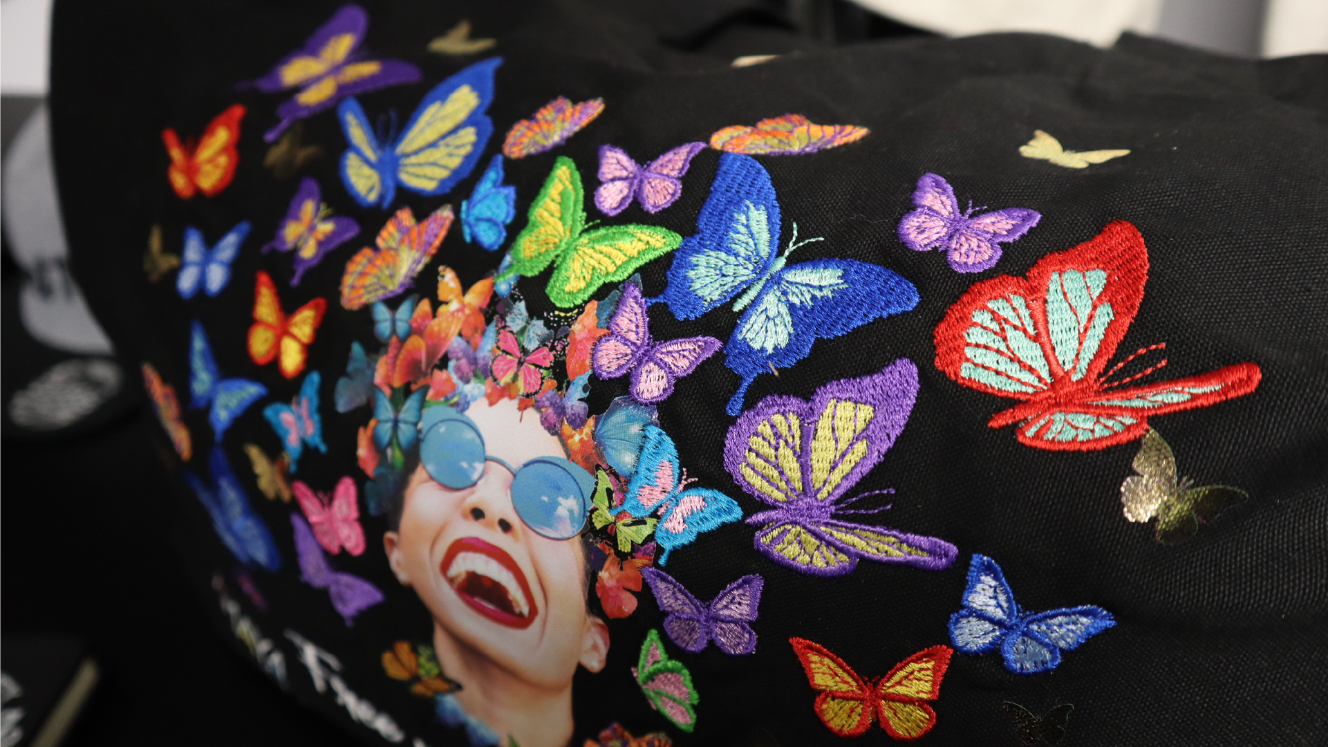 Black Tote bag with face of a woman and embroidered butterflies using Melco Embroidery Machine