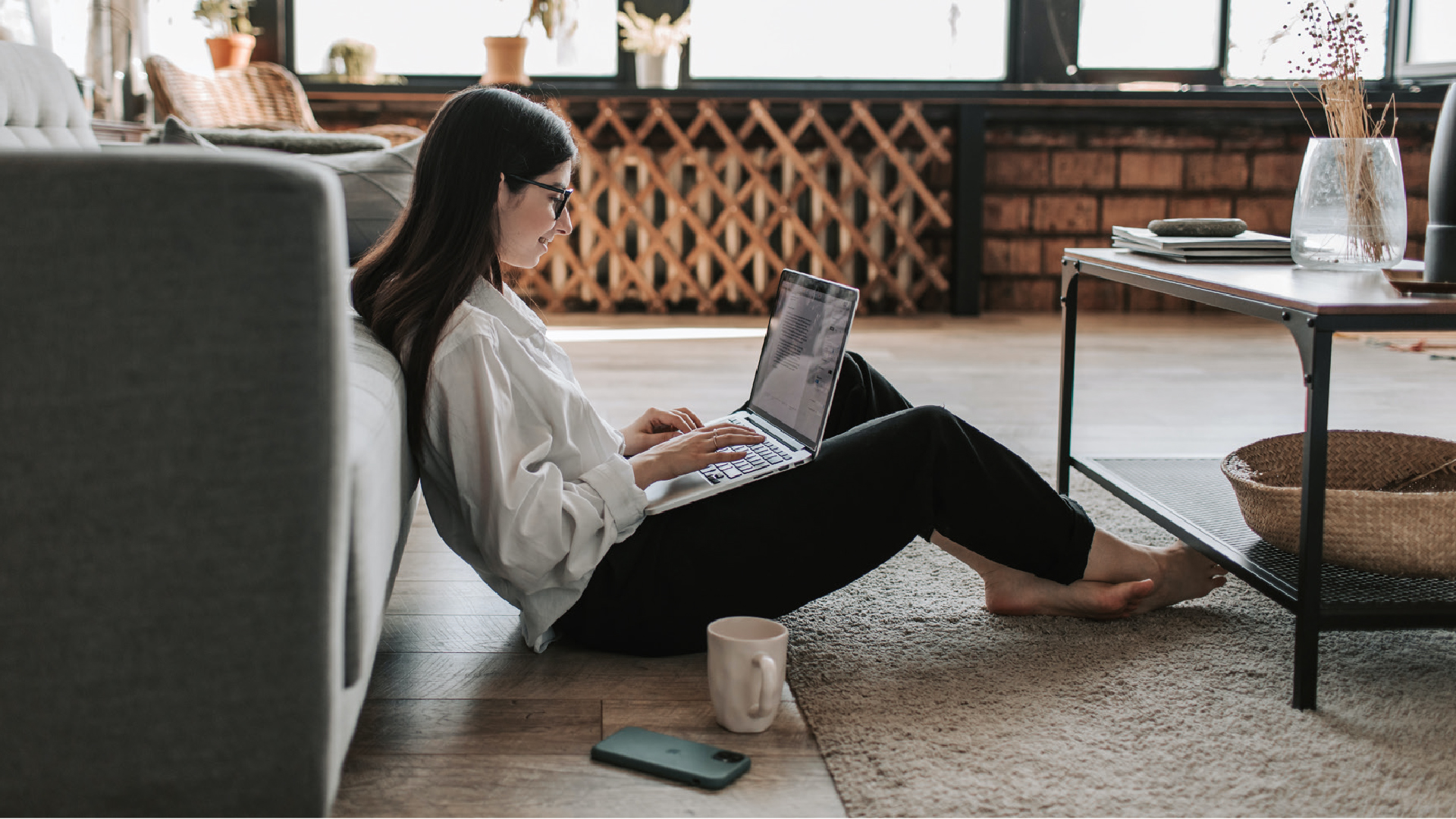 Woman sitting on floor against sofa with laptop looking happy