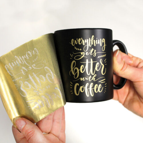 Black Mug with gold design being transferred using Forever Transfers Multi-Trans Gold Paper