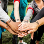 Group of peoples hands all together with team tatoos using Forever A4 Laser Tattoo Transfer Paper