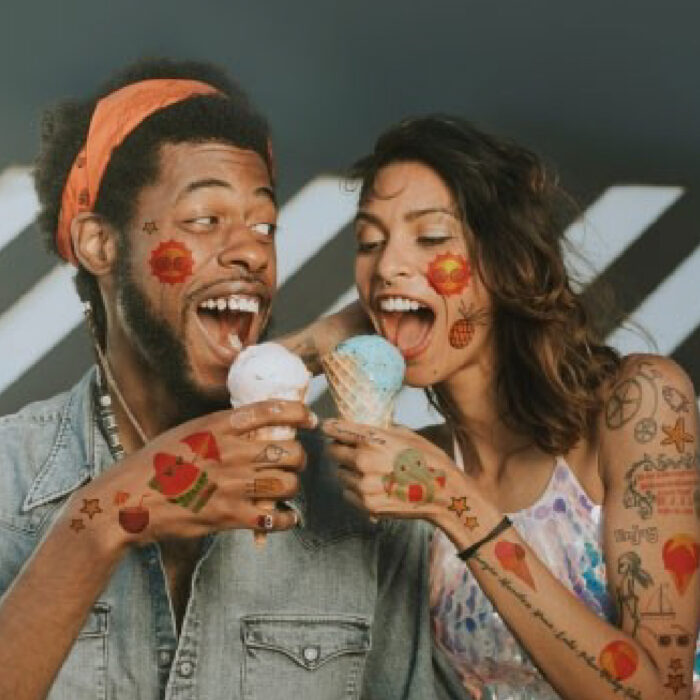 Two people sharing ice cream, covered in tattoos using Forever Tattoo Paper