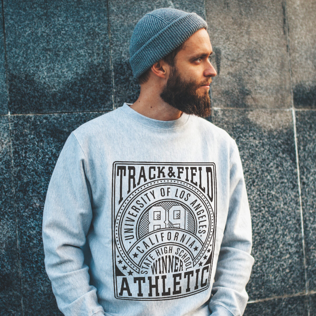 Man outside in beanie with a grey sweatshirt with a track and field print made with Forever Classic and Universal Paper