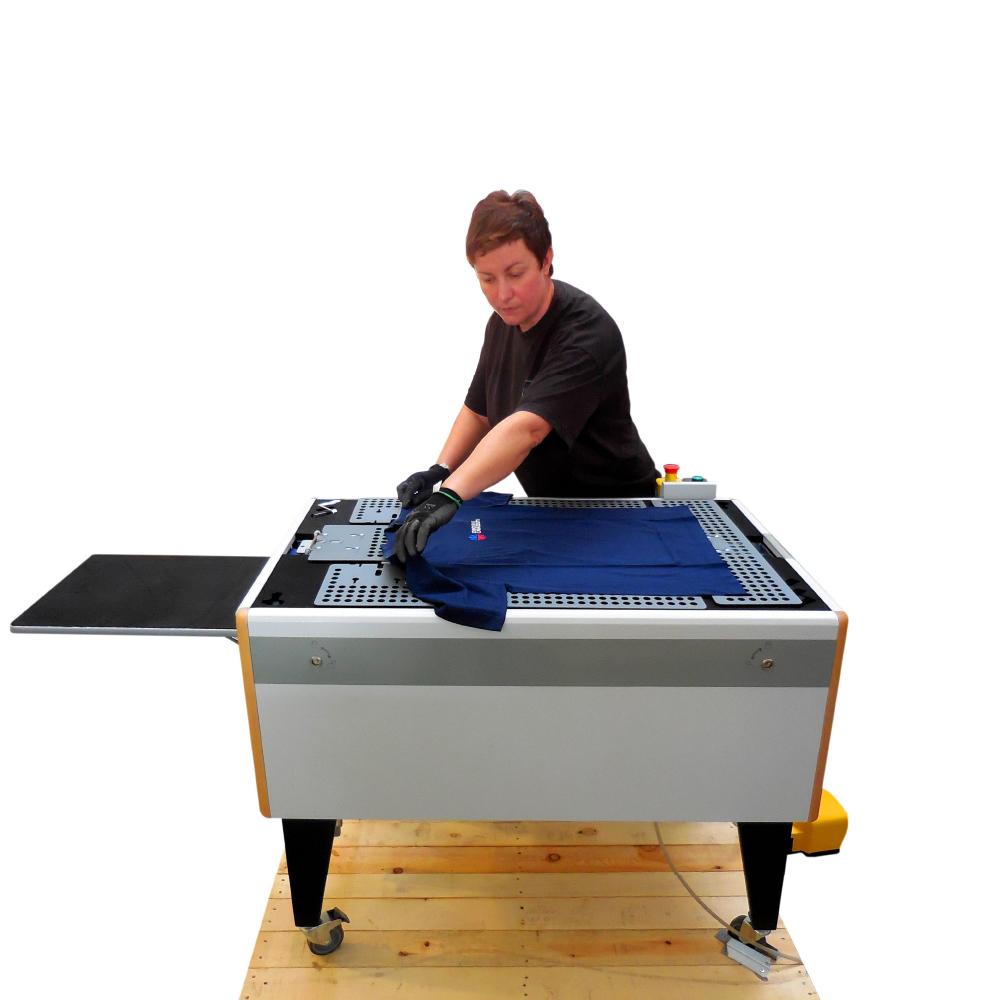 Man placing dark blue garment onto Chiossi Speedy T Folding Machine