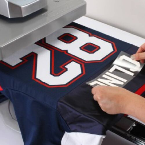 Placing transfer onto sports shirt with Stahls Hotronix Fusion IQ Heatpress
