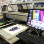 Kornit Avalanche HD6 printer with White garment design featuring beetle
