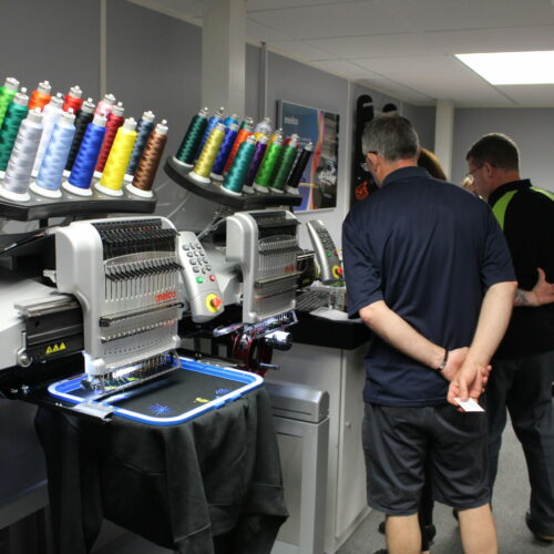 People looking at Melco EMT16X Embroidery machines in demo room